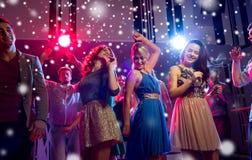 Glimlachende vrienden die in club dansen stock afbeelding