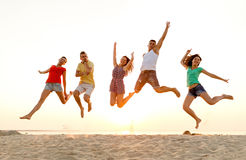 Glimlachende vrienden die en op strand dansen springen Stock Fotografie