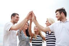 Glimlachende vrienden die hoog gebaar vijf in openlucht maken Stock Afbeelding