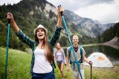 Glimlachende vrienden die met rugzakken lopen Avontuur, reis, toerisme, stijging en mensenconcept stock afbeeldingen