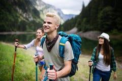 Glimlachende vrienden die met rugzakken lopen Avontuur, reis, toerisme, stijging en mensenconcept stock foto's