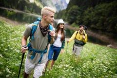 Glimlachende vrienden die met rugzakken lopen Avontuur, reis, toerisme, stijging en mensenconcept stock foto