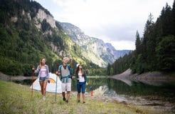 Glimlachende vrienden die met rugzakken lopen Avontuur, reis, toerisme, stijging en mensenconcept stock afbeelding