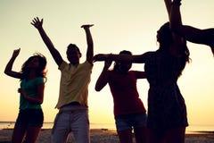 Glimlachende vrienden die op de zomerstrand dansen Royalty-vrije Stock Foto