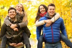 Glimlachende vrienden die pret in de herfstpark hebben Stock Afbeeldingen