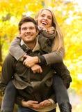 Glimlachende vrienden die pret in de herfstpark hebben Stock Fotografie