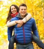 Glimlachende vrienden die pret in de herfstpark hebben Stock Foto