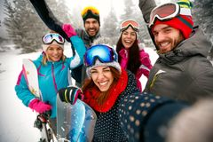 Glimlachende vrienden die pret hebben Snowboarders en skiërs die selfi maken Stock Afbeelding