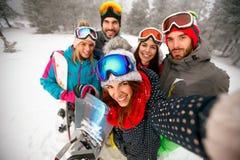 Glimlachende vrienden die pret op de winter hebben hodays Snowbarders en ski Stock Afbeeldingen