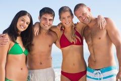 Glimlachende vrienden die samen stellen Stock Foto
