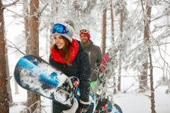 Glimlachende vrienden die snowboarder door in de mistwinter vooraan gaan Stock Fotografie