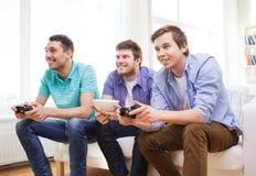 Glimlachende vrienden die videospelletjes thuis spelen Royalty-vrije Stock Fotografie