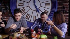 Glimlachende vrienden die wijn en het eten drinken stock footage