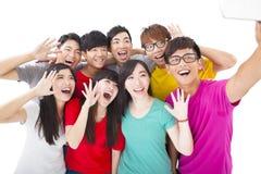 Glimlachende vrienden met camera die zelffoto nemen stock afbeelding
