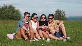 Glimlachende vrienden met de zitting van tabletpc op gras stock video