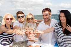 Glimlachende vrienden met glazen champagne op jacht Royalty-vrije Stock Afbeelding
