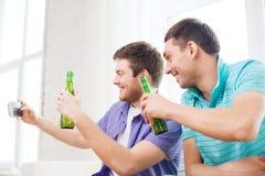 Glimlachende vrienden met smartphone en bier thuis Royalty-vrije Stock Afbeeldingen
