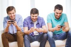 Glimlachende vrienden met smartphones thuis Stock Foto