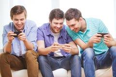 Glimlachende vrienden met smartphones thuis Royalty-vrije Stock Afbeeldingen