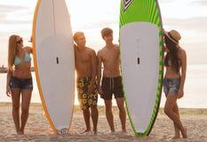 Glimlachende vrienden in zonnebril met brandingen op strand Stock Afbeeldingen