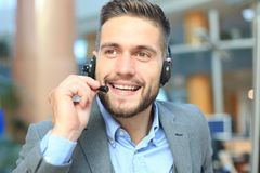 Glimlachende vriendschappelijke knappe jonge mannelijke call centreexploitant royalty-vrije stock fotografie