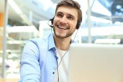 Glimlachende vriendschappelijke knappe jonge mannelijke call centreexploitant stock afbeelding