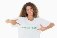 Glimlachende vrijwilliger die aan haar t-shirt richten die camera bekijken royalty-vrije stock afbeeldingen