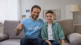 Glimlachende vrijwilliger en schooljongen die op middelbare leeftijd duim-omhoog aan camera, advertentie stoppen stock video