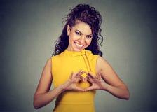 Glimlachende vrolijke gelukkige vrouw die hart maken met handen ondertekenen stock foto's