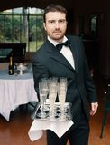 Glimlachende vrolijke kelner met glazen champagne Royalty-vrije Stock Foto