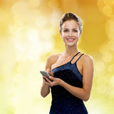 Glimlachende vrouw in avondjurk met smartphone Stock Fotografie