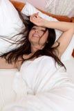 Glimlachende vrouw in bed Stock Foto
