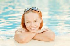 Glimlachende vrouw in bikini in pool Stock Afbeeldingen