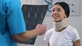 Glimlachende vrouw in cervicale kraag bij artsenbenoeming, positief x-ray resultaat stock videobeelden