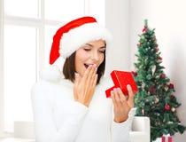 Glimlachende vrouw in de hoed van de santahelper met giftdoos Royalty-vrije Stock Foto