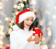 Glimlachende vrouw in de hoed van de santahelper met giftdoos Royalty-vrije Stock Afbeeldingen