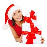 Glimlachende vrouw in de hoed van de santahelper met giftdozen Stock Afbeeldingen