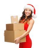 Glimlachende vrouw in de hoed van de santahelper met pakketten Royalty-vrije Stock Fotografie