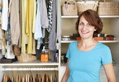 Glimlachende vrouw dichtbij kast Stock Foto's