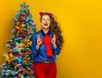 Glimlachende in vrouw dichtbij Kerstboom met gekruiste vingers Stock Foto's