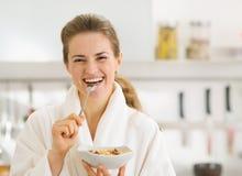 Glimlachende vrouw die in badjas gezond ontbijt eten stock fotografie