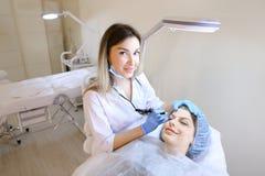 Glimlachende vrouw die bij de kosmetiekkabinet liggen en het tatoeëren van wenkbrauwen krijgen Royalty-vrije Stock Foto's