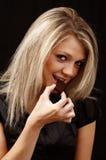 Glimlachende vrouw die chocolade eet Royalty-vrije Stock Foto's