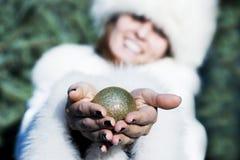 Glimlachende vrouw die de bal van de Kerstmisboom met handen geven Royalty-vrije Stock Afbeelding