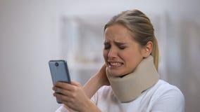 Glimlachende vrouw die in de lezingsbericht van de schuim cervicaal kraag op telefoon halspijn voelen stock video