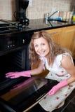 Glimlachende vrouw die de oven schoonmaakt stock fotografie