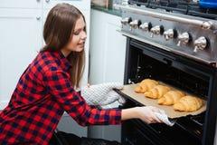 Glimlachende vrouw die dienblad met croissants van oven thuis nemen stock afbeeldingen