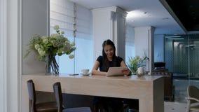 Glimlachende vrouw die digitale tablet gebruiken terwijl het zitten in een koffie stock videobeelden