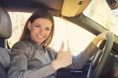 Glimlachende vrouw die duim in auto tonen stock foto