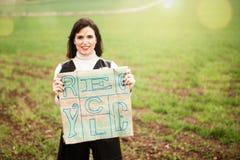 Glimlachende vrouw die eco vriendschappelijke zak met Kringloop gedrukte teksten tonen Royalty-vrije Stock Fotografie